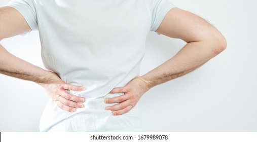 Back pain. Medical and pharmaceutical concept. The man is holding his back, feeling severe pain.