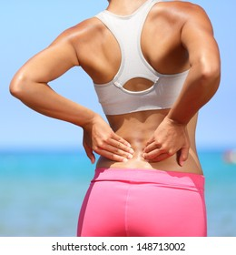 Back pain - woman having painful muscle injury in lower back. Fitness girl sport girl with sports injury outdoor on beach.
