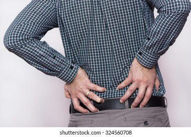 Back pain.  Young businessman suffering back pain.