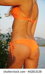 Back part of a girl's in orange bikini