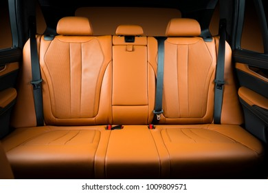 Back passenger seats in modern luxury car, frontal view, redo perforated leather with stitching