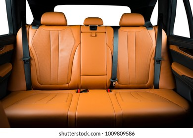 Back passenger seats in modern luxury car, frontal view, redo perforated leather with stitching, isolated windows with clipping path