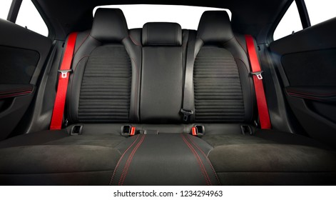 Back passenger seats in modern luxury car, frontal view, black leather, alcantara and red belts. Isolated with clipping path