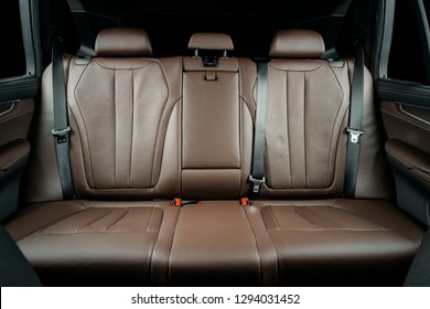 Back passenger seats in modern luxury car, frontal view, red perforated leather, isolated on black, clipping path included.