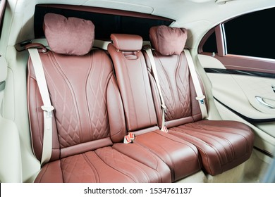 Back passenger seats in modern luxury car inside interior, red perforated leather