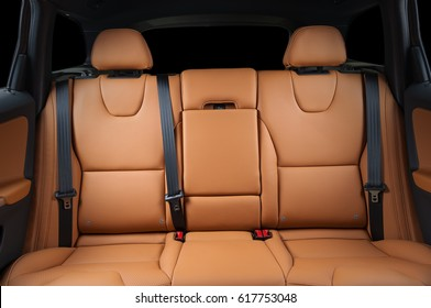 Back passenger seats in modern luxury car, frontal view, red leather