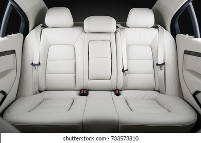Back passenger seats in modern luxury car, frontal view, white leather, isolated, clipping path included
