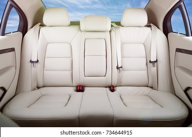 Back passenger seats in modern luxury car, frontal view, blue sky in the windows, lens flare effect