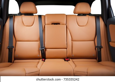 Back passenger seats in modern luxury car, frontal view, red sand leather