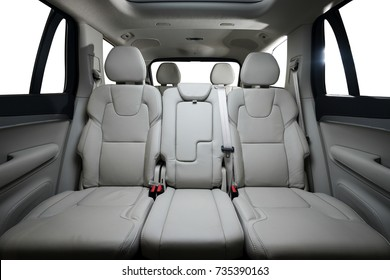 Back passenger seats in modern luxury car, frontal view, white leather, isolated on white, clipping path included.