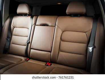 Back passenger seats in modern luxury car, frontal view, Red leather, isolated on black, clipping path included.