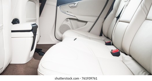 Back passenger seats in modern luxury car, white leather