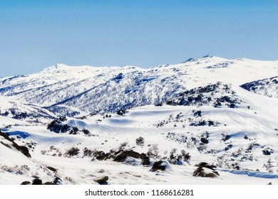 Back Perisher mountain peak and nearby ranges around Perisher valley high in Snowy mountains of Australia in their beauty during winter season with lots of white snow.