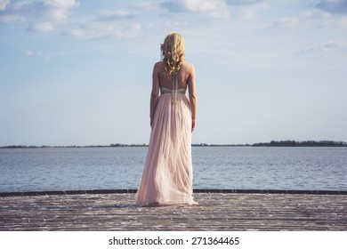 Back portrait of beautiful blond curly woman wearing evening peach color gown at lake.Fashionable and glamorous dress with chains.