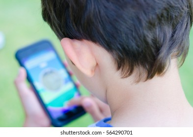 Back Portrait Close up young boy playing alone on smartphone in blurred background, internet and social media addiction concept.