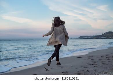 Back portrait girl running on sea beach in stylish wear, stylish wear, skin care, brunette hipster enjoy the sea, happy model, dreamer, girl in white shirt, laugh, bohemian woman resting, hand watch