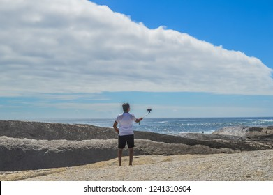 Back portrait of an Indian young male taking selfie on a big rock on Camp's bay near Maiden's cove beach