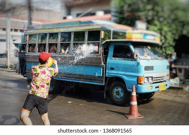 Back portrait man splashes the water into the traditional bus on the road  in Songkran festival.