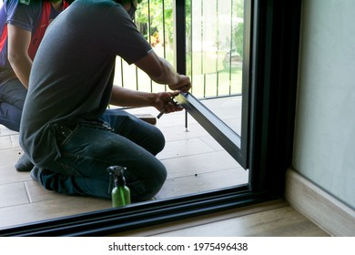 Back portrait of worker repairs the frame of aluminum door in the house