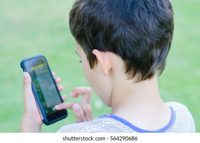 Back Portrait  young boy playing alone on smartphone in blurred background, internet and social media addiction concept.