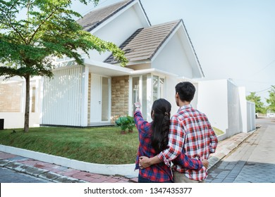 back portrait of young couple standing in front of their new house