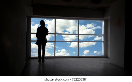 Back or rare view of women silhouette beside the big window and sky with cloud background,freedom concept