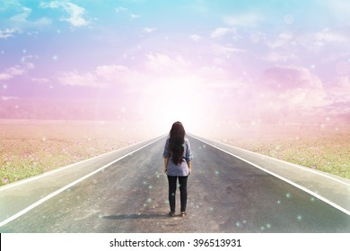 Back or rare of women standing on pavement road with dreamy morning sunlight background with copy space, concept road to heaven, freedom, road to happiness, way of women
