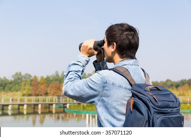 The back rear of man using binoculars for birdwatching
