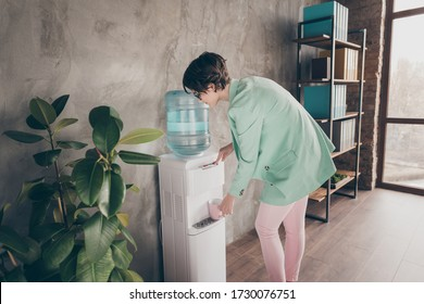 Back rear spine profile side photo of charming positive girl agent broker lawyer want drink fill water mug cooler gallon press button wear blazer jacket pink trousers pants in workplace