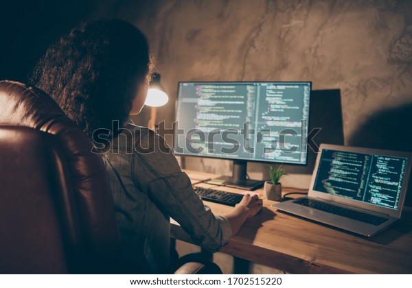 Back rear spine view photo concentrated afro american girl company administrator sit evening desk table lamp use computer work data debugging improvement binary algorithm code in workstation