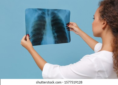 Back rear view of african american doctor woman in medical gown hold X-ray of lungs fluorography roentgen isolated on blue background. Healthcare personnel medicine health concept. Mock up copy space