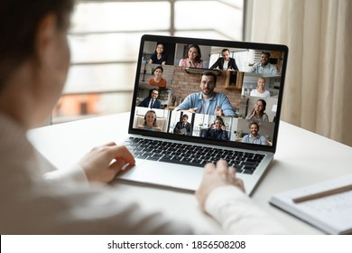 Back rear view focused young female employee involved in video conference brainstorming meeting with diverse happy colleagues and male team leader, working from home using computer application. - Shutterstock ID 1856508208