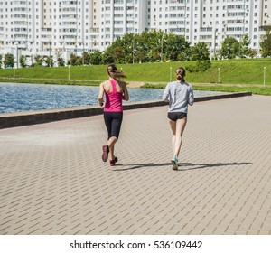 back rear view. sports woman couple run at park in the morning. two girl run together against park with summer green grass background and house backdrop. pair female running alond water line of coast