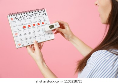 Back rear view woman in dress hold in hand thermometer, female periods calendar checking menstruation days isolated on pink background. Medical healthcare, ovulation gynecological concept. Copy space