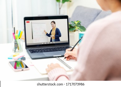 Back rear view of young asian girl sit on desk and learn at home living room in concept of romote learning, virtual online, self isolated quarantine lifestyle in asia. Teaching video call on computer.
