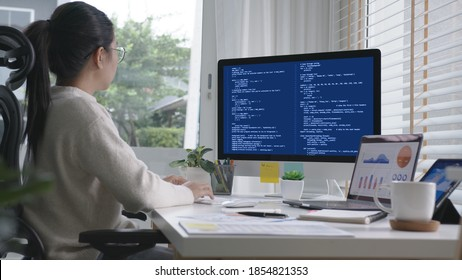 Back rear view of young asian woman, freelance data scientist work remotely at home coding programing on Big data mining, AI data engineering, IT Technician Works on Artificial Intelligence Project.