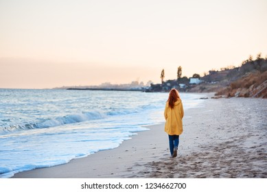 the back of a red-haired girl in a yellow rain coat walking along the seashore