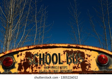 Back of rusting school bus in a junkyard with blue sky in winter Rockwood, Ontario, Canada - March 27, 2011