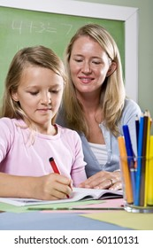Back to school - 8 year old student and teacher writing in classroom
