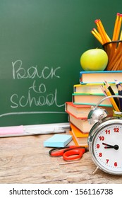 Back to school. School accessories against a school board.