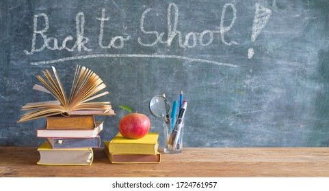 Back to school after the coronavirus pandemic lockdown, education supplies, books, pens, message on blackboard