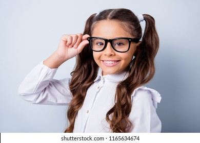 Back to school again! Portrait of nice cute funny cheerful adorable lovely stylish small little girl with two curly ponytails in white shirt, wearing, touching glasses. Isolated over grey background