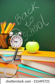 Back to school. An alarm clock, an apple and school accessories against a school board.