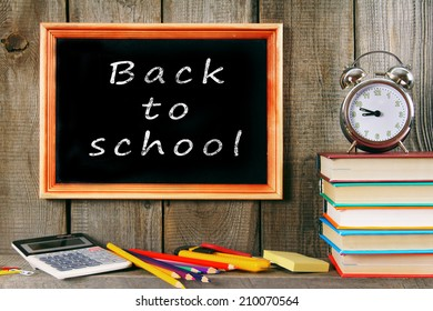 Back to school. An alarm clock, books and other school accessories. On a wooden background.