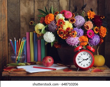 Back to school. Alarm clock, bouquet, apples, and books on the table.  The teacher's day. The day of knowledge. September 1.