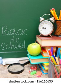 Back to school. An apple, an alarm clock and other school tools against a school board.