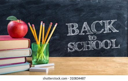 back to school - apple on books with pencils and blackboard