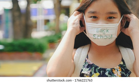 Back to school. asian child girl wearing face mask with backpack  going to school .Covid-19 coronavirus pandemic.New normal lifestyle.Education concept.