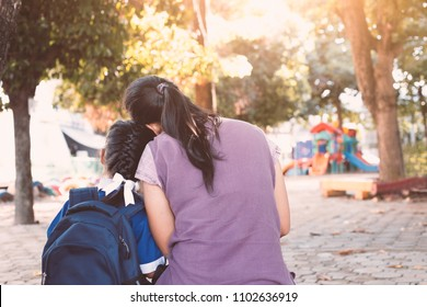 Back to school. Asian mother and daughter with backpack sitting together in the playground before go to classroom in the school.