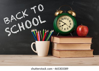 Back to school background with alarm clock, books, apple and pencils